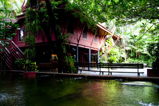 Red house on stilts surrounded by lush vegtation