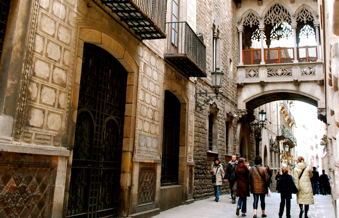 A small crowd wanders through the Gothic streets of Barcelona.