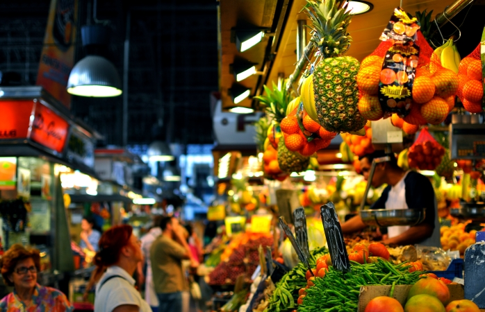 Shoppers wander passed a fruit food stall at the Boqueria market.