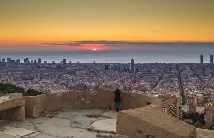 A woman watches the sunrise on top of Barcelona's Bunkers del Carmel