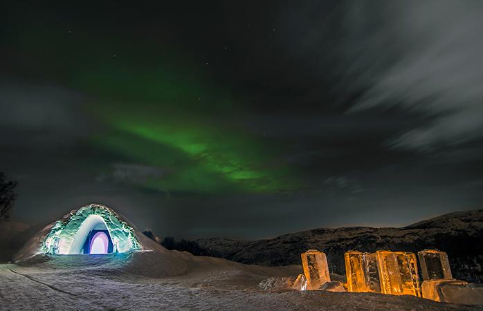 The Northern Lights twinkle over the Kirkenes Snowhotel in Sor-Varanger, Norway.