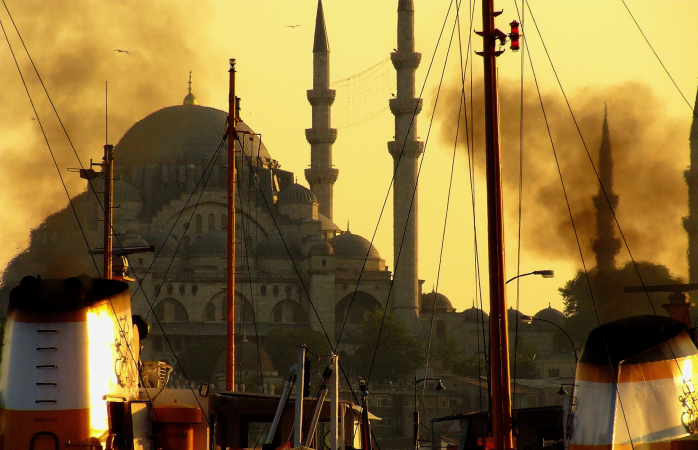 Smoky boats on the Bosporus with the imposing New Mosque in the background.