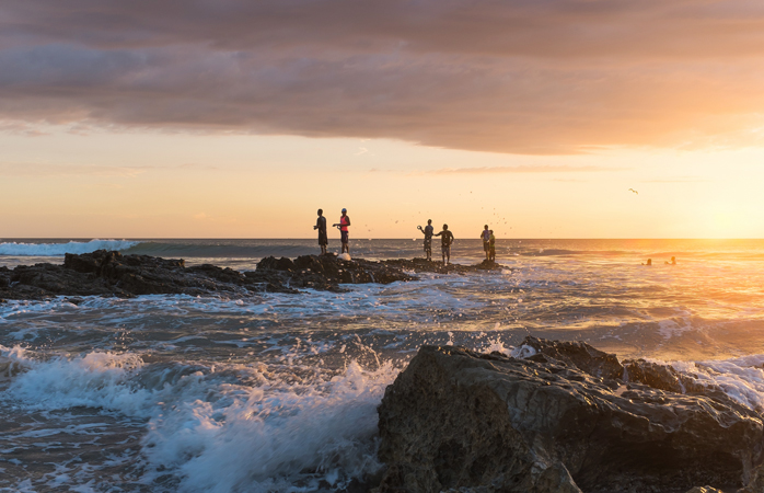 A troupe of fisherman try to catch some exotic fish off the craggy beachfront.