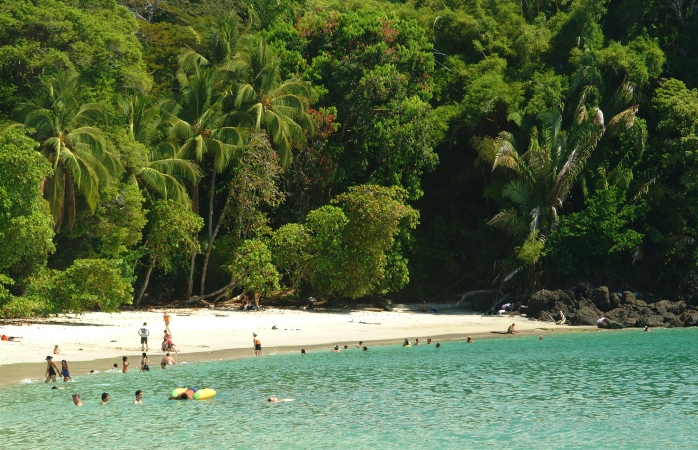 A small crowd of sun searchings lounge and swim on the Playa Manuel Antonio, Costa Rica.