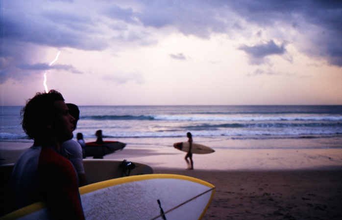 A group of surfers get ready to head out into the ocean.