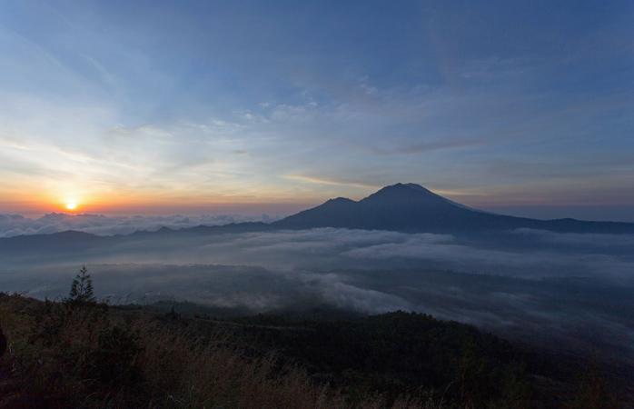 Barely peeking : Mount Batur through the morning clouds