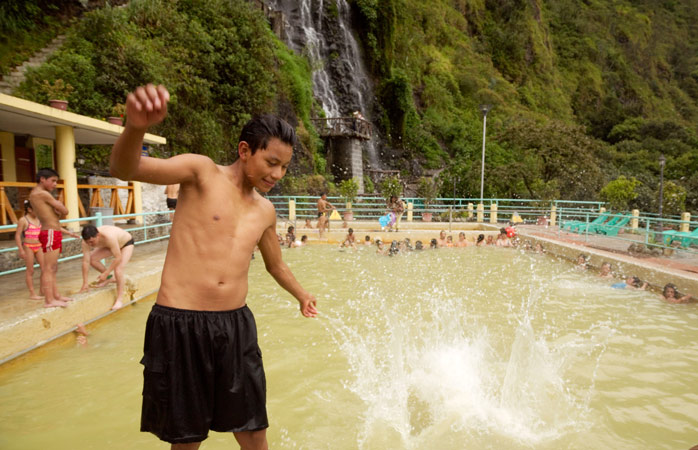 Mingle with locals at the thermal baths in Baños, complete with a view of the waterfall