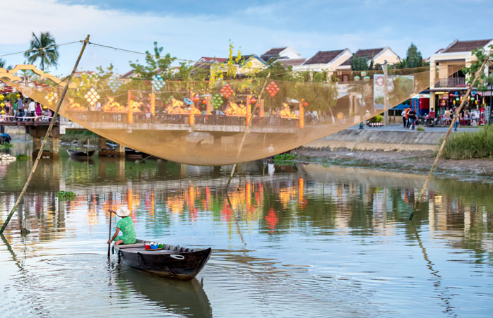 A man travels in a traditional Vietnamese fishing boat in Hoi An, Vietnam