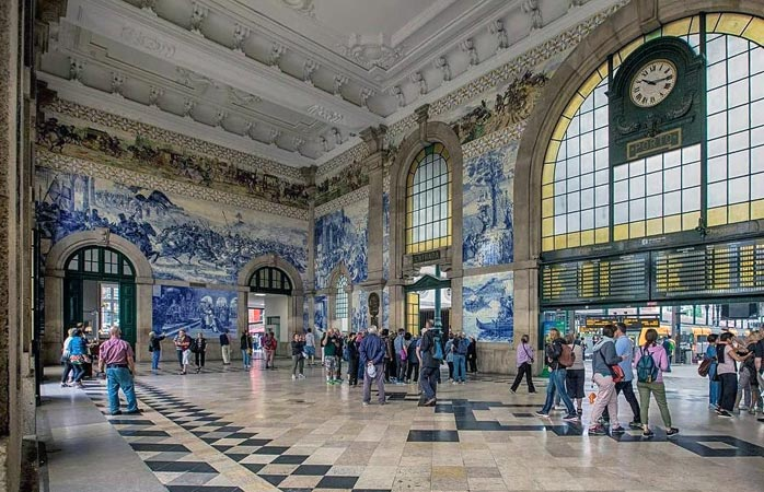 Tourists stop to admire the beautiful azulejo tiles inside the São Bento Train Station in Porto © suitcase_and_wanderlust