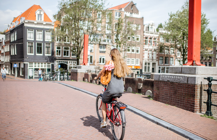 A young woman bicycles across the canal - Amsterdam, The Netherlands