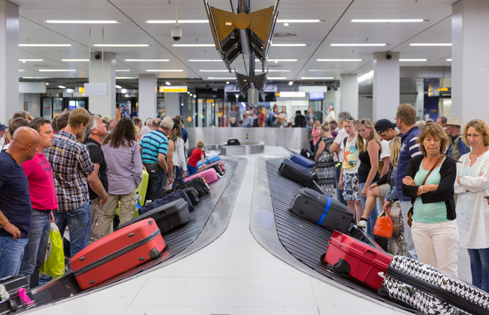 Passengers wait patiently to pick up their luggage from baggage claim at Schiphol Airport - Amsterdam, Netherlands