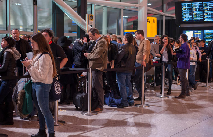 Passengers wait in line for their flights at Heathrow Airport - London, UK
